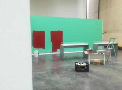 Sala de exposiciones que muestra una escalera y un cambio de color en las paredes